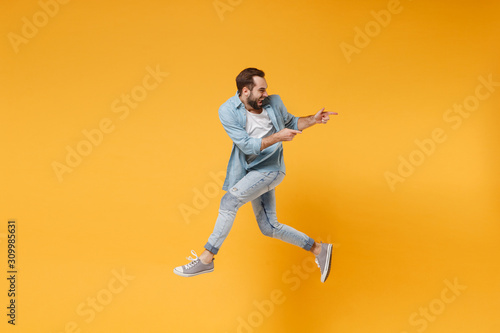 Fototapeta Funny young bearded man in casual blue shirt posing isolated on yellow orange background, studio portrait