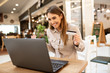 Cute young caucasian brunette woman smiling while online shopping on her laptop. She's cheerful, happy, looking at her laptop, holding her credit card and sitting in a coffee shop.