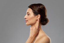 Hearing, People And Beauty Concept - Beautiful Young Woman Pointing Finger To Her Ear Over Grey Background