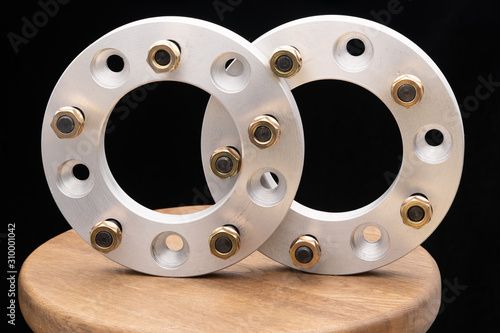 Fototapeta Automotive parts - close up new stainless metal remote adapter spacer wheel hub of the car on black background obraz