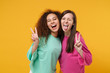 canvas print picture - Two cheerful women friends european and african american girls in pink green clothes posing isolated on yellow orange background. People lifestyle concept. Mock up copy space. Showing victory sign.