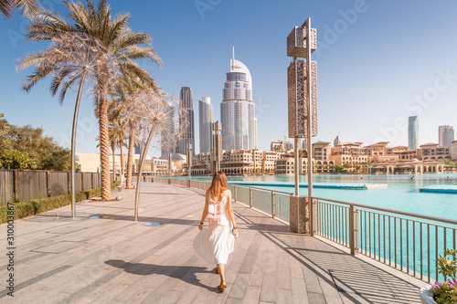 Fototapeta Happy tourist girl walking near fountains in Dubai city