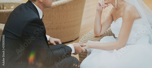 young, european, beautiful couple in wedding suits, sit opposite each other and gently hold hands Canvas Print