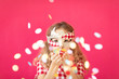 canvas print picture - Fancy girl blowing confetti against pink bakground