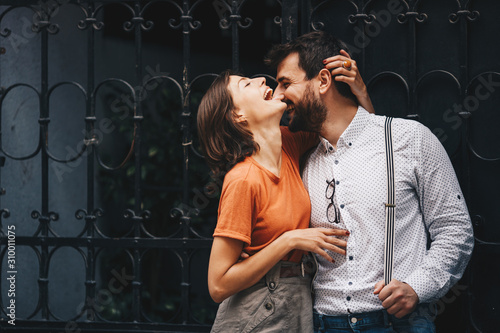 Fototapeta Young attractive Caucasian couple embracing, laughing and enjoying their romantic date while standing by the iron fence