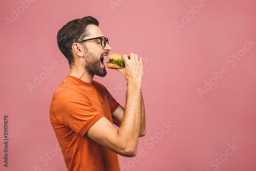 Canvas Print Young man holding a piece of hamburger