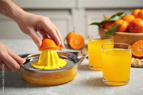 Fototapeta Woman making fresh tangerine juice indoors, closeup obraz