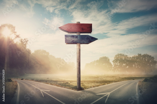 Photo Surreal landscape with a split road and signpost arrows showing two different courses, left and right direction to choose