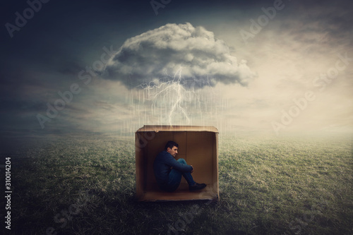 Surreal concept with a scared guy shelters inside a cardboard box Fotobehang