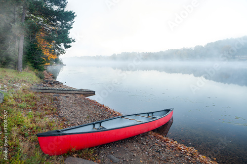 A lone canoe pulled up on the shores of Oxtounge river during a fall early morni Wallpaper Mural