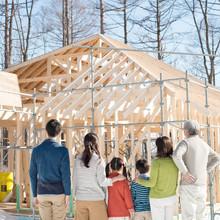 建設途中の家を眺める3世代家族の後姿