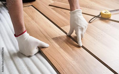 Obraz na plátně Installing laminated floor, detail on man hands in gloves fitting wooden tile, o