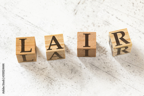 Four wooden cubes with letters LAIR (meaning Listen Acknowledge Identify Reverse) on white working board Canvas Print