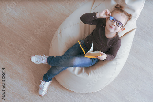 Cute caucasian girl in glasses sitting on a bean bag and holding book Wallpaper Mural
