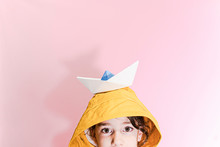 Little Girl Wearing An Oilskin And Carrying A Paper Boat On Her Head