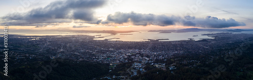 Photo A serene sunset illuminates the densely populated San Francisco Bay area including Oakland, Berkeley, Emeryville, El Cerrito, and San Francisco in the distance