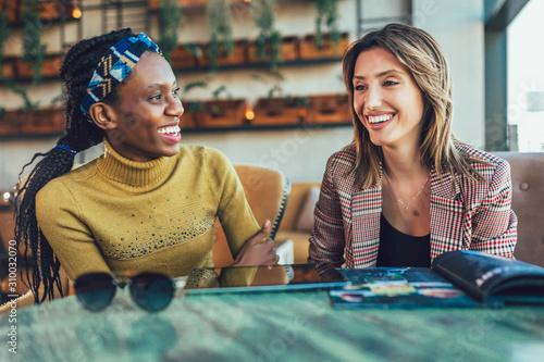 Obraz Two female friends talking at a coffee shop - fototapety do salonu