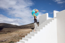 Little Girl On White Stairs, Carrying Inflatable Globe
