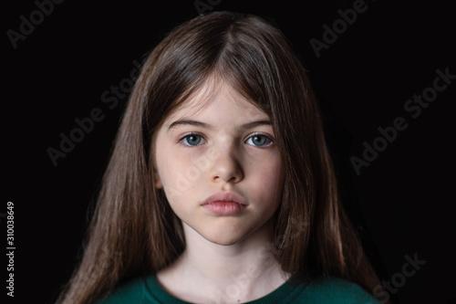 Valokuva Closeup portrait of serious, sad little girl isolated on black background