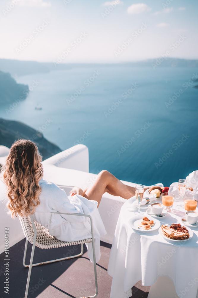 Fototapeta Young woman with blonde hair having breakfast in santorini greece