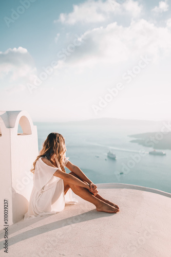 Fototapeta Young woman with blonde hair on rooftop in santorini greece obraz