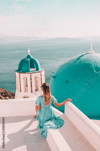Fototapeta Young woman with blonde hair and blue dress in oia, santorini, greece with ocean view and churches obraz