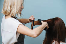 Blonde Female Hairdresser In Apron Straightening Client's Brown Hair With Flat Iron Over Blue Background. She's Pulling Her Hair With A Comb To Control A Process. Side View.