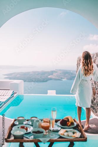 Fototapeta Woman having breakfast by the pool in santorini, greece obraz