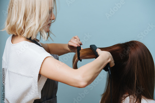 Canvas Print Blonde female hairdresser in apron straightening client's brown hair with flat iron over blue background