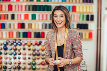 Portrait Of Happy Dressmaker Woman In Studio. Background Of Colorful Sewing Thread.