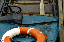 A Lifeboat Moored Near A Wooden Pier. Inside Is A Wooden Oar And A Life Preserver. An Old Motorboat With A Steering Wheel. Poor Working Conditions. Use Of Old Equipment.