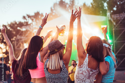 Back view of female friends at music festival drinking beer and dancing