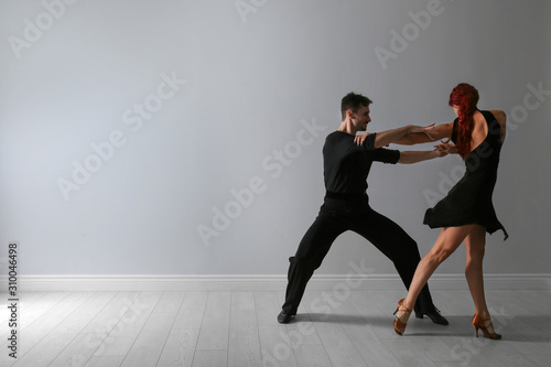 Beautiful young couple dancing near light wall. Space for text Fototapete