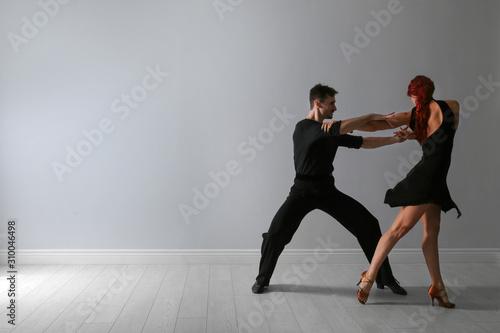 Fototapeta Beautiful young couple dancing near light wall. Space for text