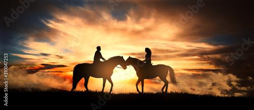 Photo Couple on horseback at sunset