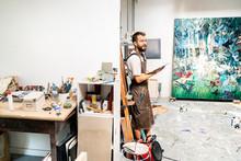 Artist Standing In His Studio, Holdong Digital Tablet