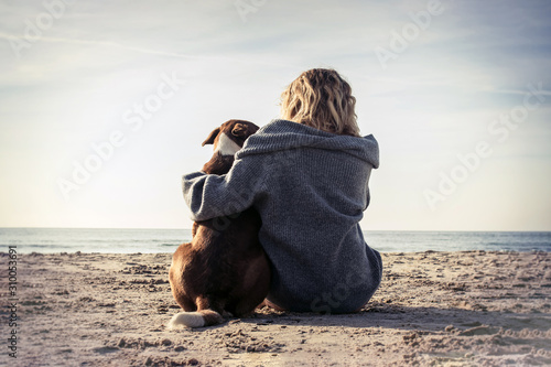 Young woman sitting and hugging dog on the beach Wallpaper Mural