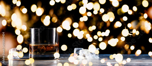 Glass of whiskey on the rocks with some ice on the table Canvas Print