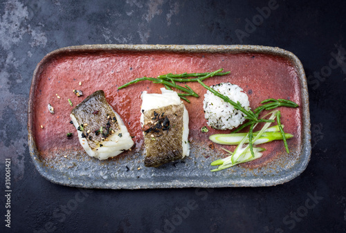Gourmet fried Japanese skrei cod fish filet with glasswort and furikake onigiri as top view on a modern design plate