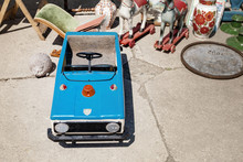 Various Vintage Old Staff ,collectibles And Toys At Weekend Open Air Swap Meet Marketplace At Bright Sunny Day. Retro Children Convertible Ussr Soviet Toy Car For Sale At Outdoor Flea Market