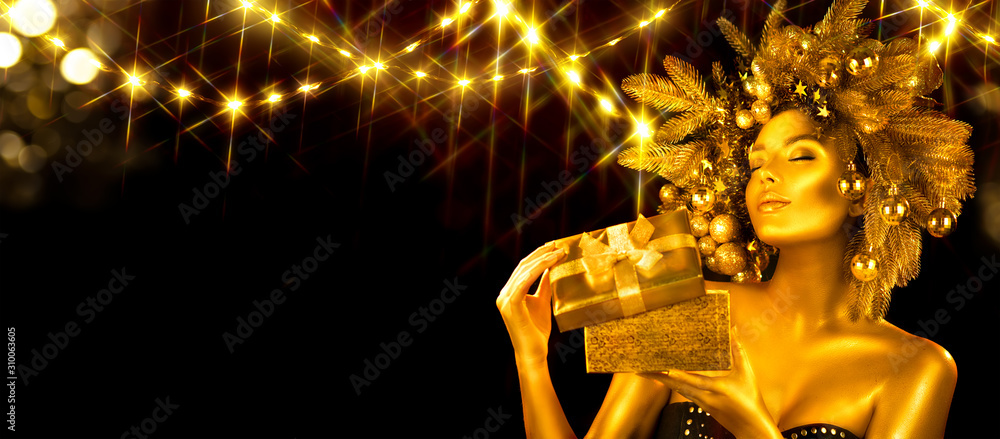 Christmas golden Woman. Winter girl receiving gift, opening magic box,  Beautiful New Year, Christmas Tree Holiday Hairstyle and gold skin Makeup. Girl in decorated Xmas wreath. Beauty surprised Model