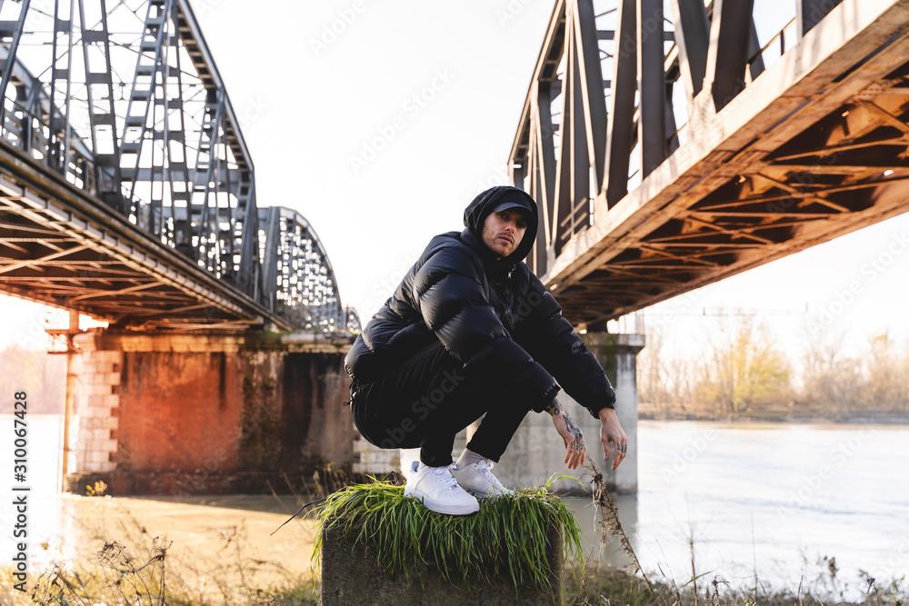 Fototapeta portrait of young rapper posing under a metal bridge