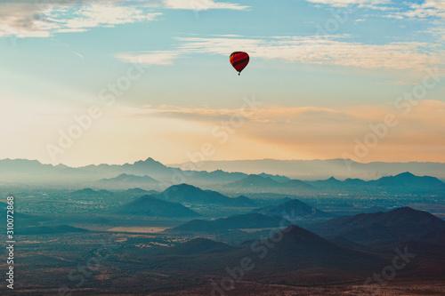 Obraz na plátně Hot Air Balloon floating over the Misty Mountains of the Arizona Desert near Pho