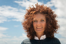 Close Up Portrait Of Beautiful Woman With Curly Red Hair Against Blue Sky.