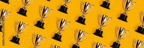 Fotografie, Tablou Champion cup on yellow background, Flat lay style