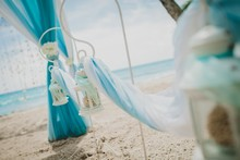 White And Blue Wedding Decorations On A White Table On A Beach With The Sea On The Background