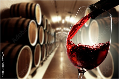 Fototapeta Red wine being poured in wineglass on background obraz