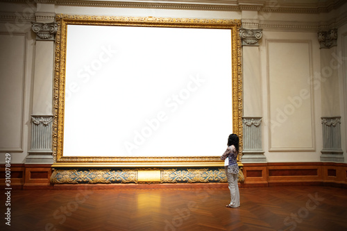 Leinwand Poster Woman with folded arms standing in front of and looking at big blank painting canvas with huge frame with negative area for your art and text