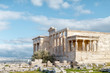 Panoramic view on the ruins of Erechtheion temple. Acropolis Hill in Athens. The surviving part of the colonnade. Figures of Caryatids Porch. Female statues. Blue sky. Traveling and vacation concept.