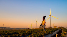 One Woman Stands In The Middle Of A Wide Field Have Large Wind Turbines, Which Is An Industry That Produces Electricity From Clean Energy.